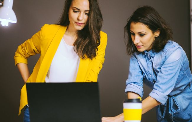 Two women at desk working on computer
