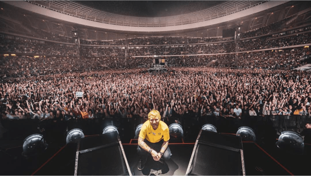Ed  Sheeran crouched in front of massive Cape Town crowd.