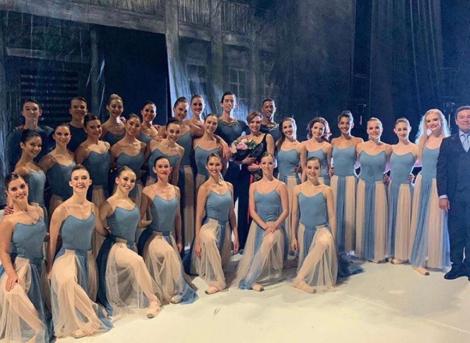 A large group of ballet dancers, posing for an image on stage.