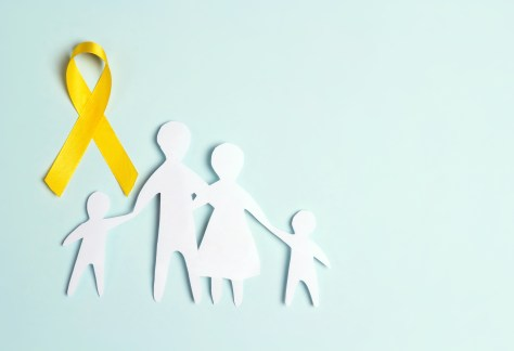 Paper family silhouette with yellow awareness ribbon on a blue background. Suicide prevention and Childhood Cancer Awareness concept.