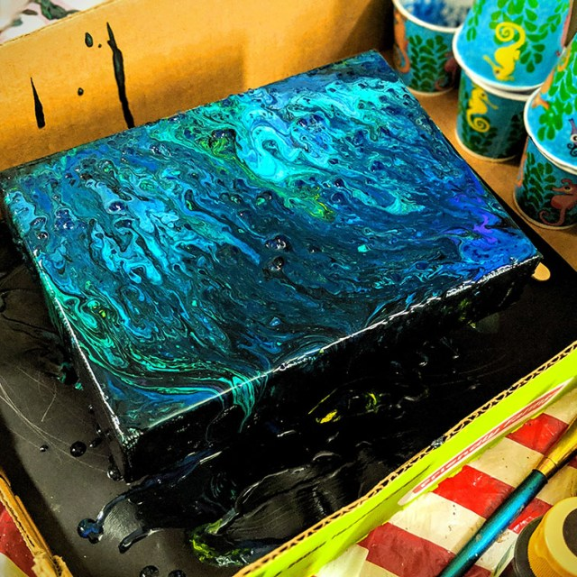 Blue poured acrylic paint on canvas