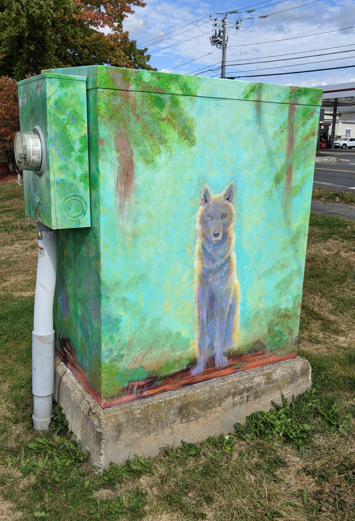 Finished electric box mural front with imprersiionistic wolf on a glowing blue background surrounded by woods.