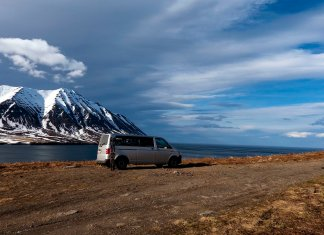 A van parked by the sea.