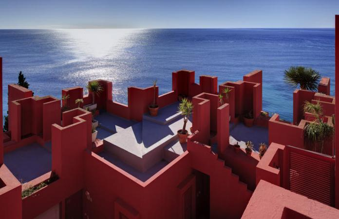 Shades of the World: The Red Walls of La Muralla Roja overlooking a beach