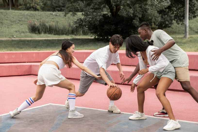 positive young diverse teenagers playing basketball on outdoor court