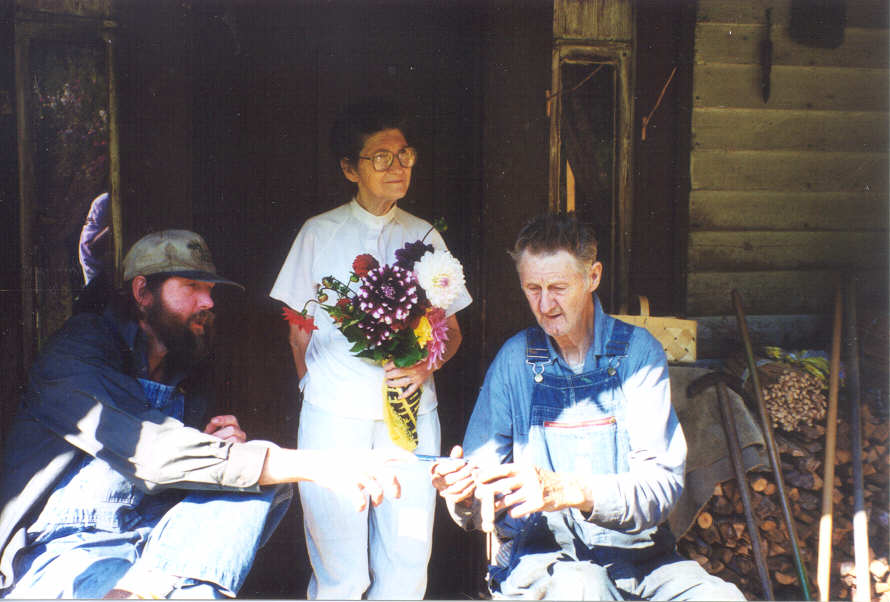 Rosa with a dahlia, Ted, and Ray on the front porch