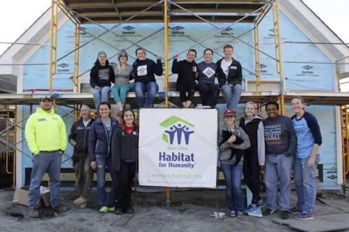 Students of Habitat for Humanity gather in front of their work done in Minneapolis