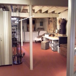 Basement with an open space plan has a hidden workshop area tucked behind two tall cabinets at Stow and Tell U