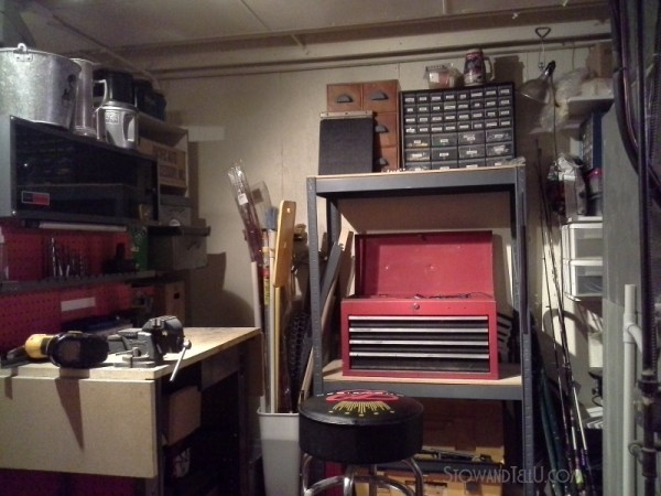 A small, open plan basement with a hidden workshop nook using two tall cabinets as the buffer also hiding the furnace at Stow and Tell U.com.
