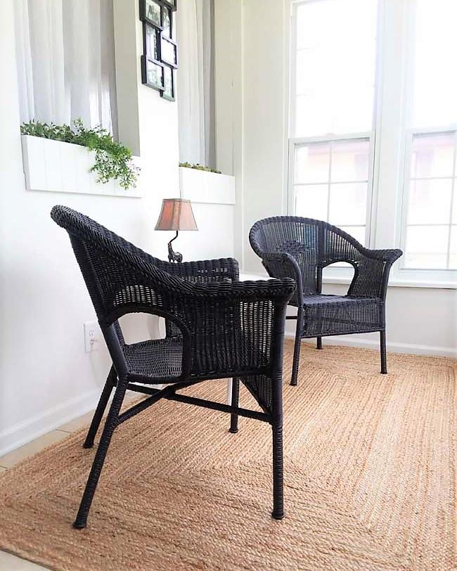 Black wicker chairs on small sun porch