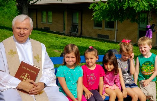 Fr. Marc Pasiak sits with Pre-K students on the Buddy Bench