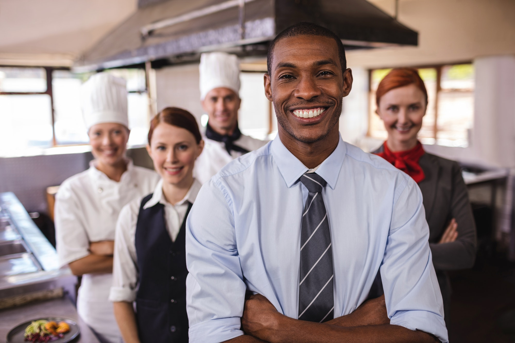 Group of hotel staffs standing with arms crossed in kitchen
