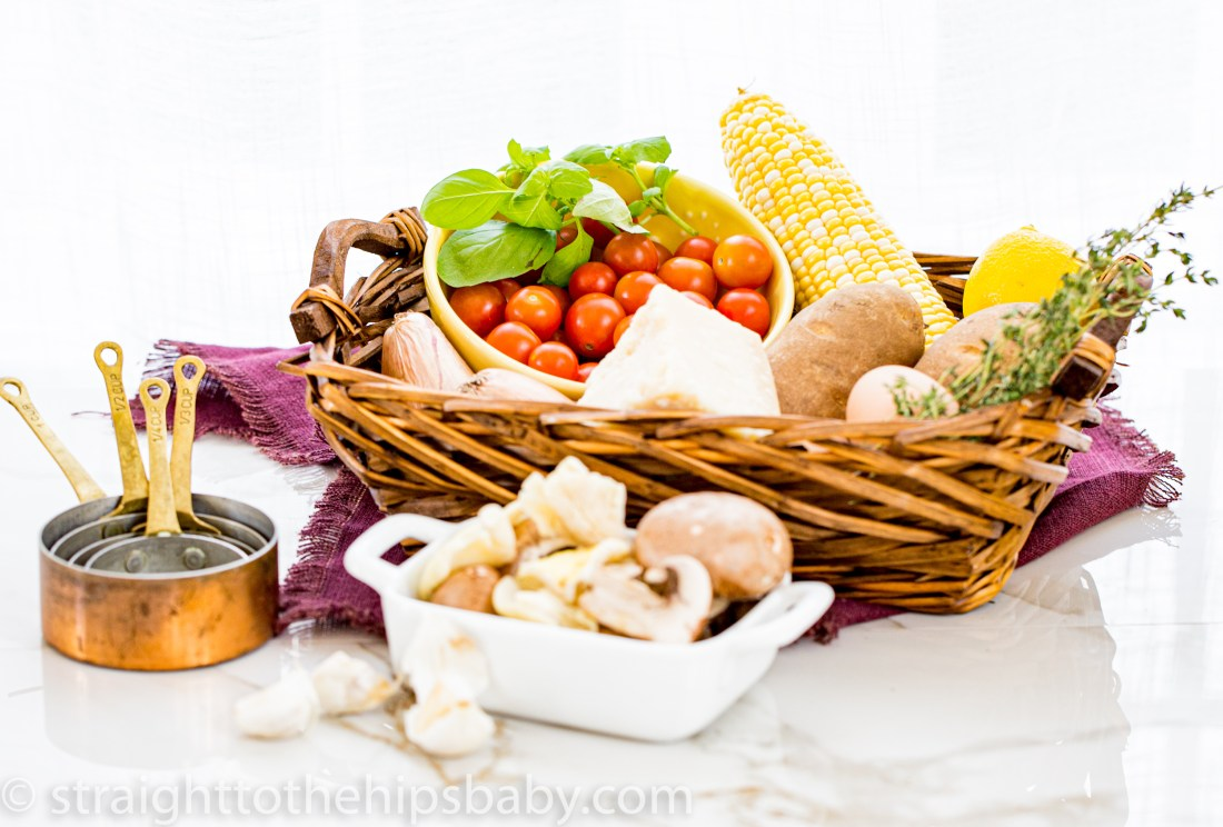 an overflowing basket of vegetables an herbs, with copper measure cups in the foreground