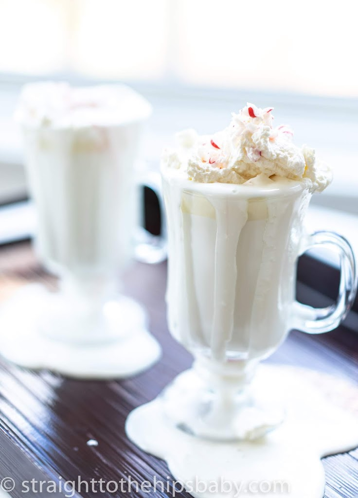 two overflowing glass mugs of peppermint white hot chocolate with whipped cream and peppermint pieces