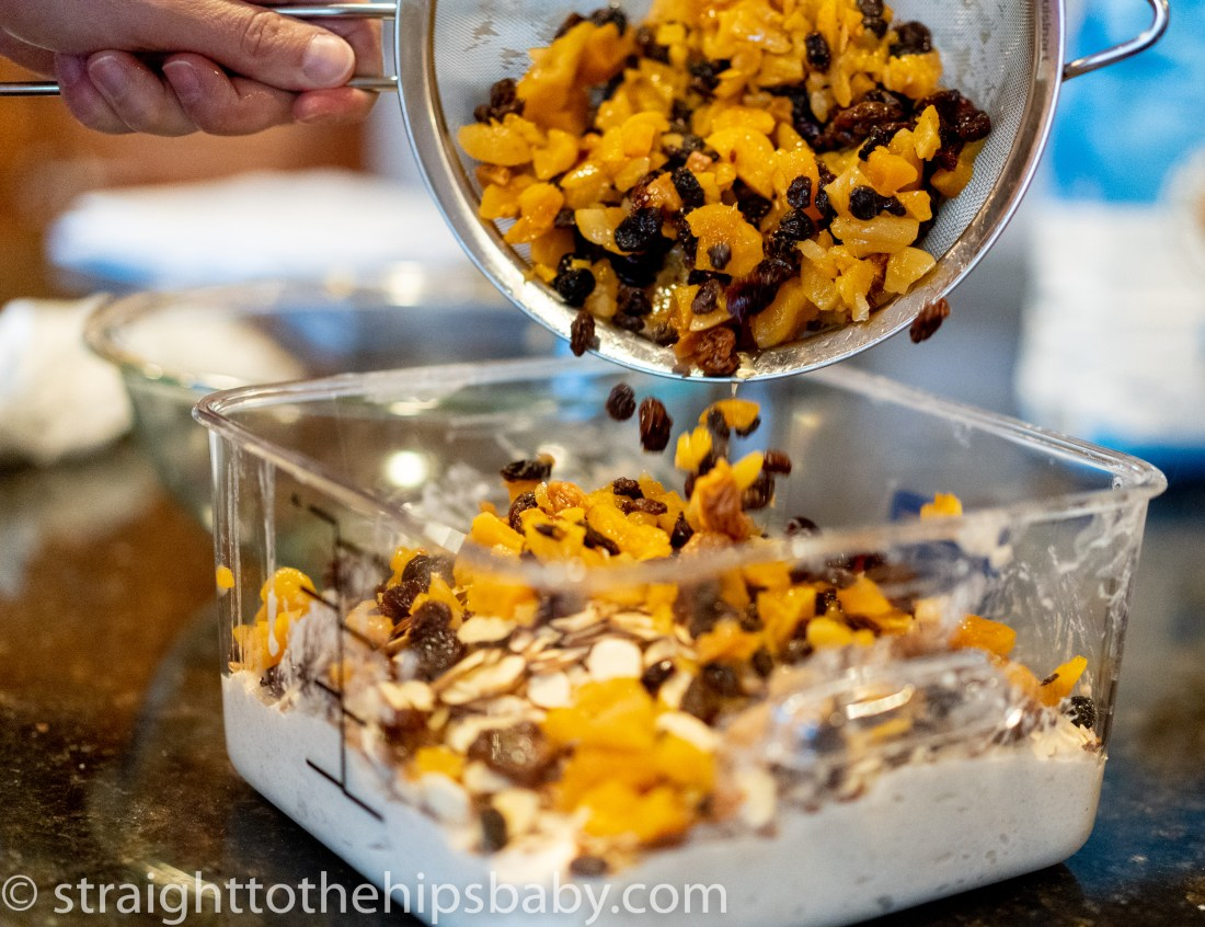 adding the rehydrated fruits to the dough to make the dried fruit and nut sourdough bread