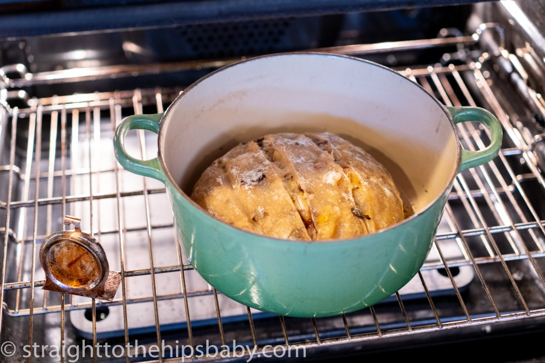 a large green pot with an uncooked loaf of bread, resting on the middle oven rack