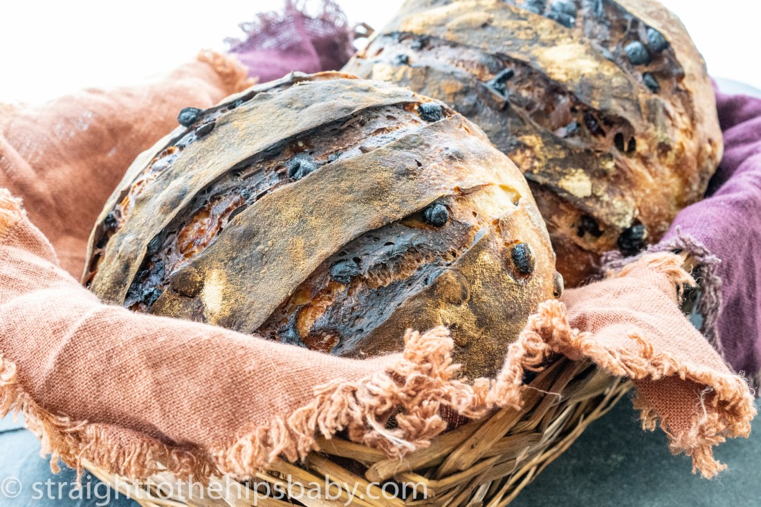 two browned dried fruit and nut boules, in a basket with colorful linens