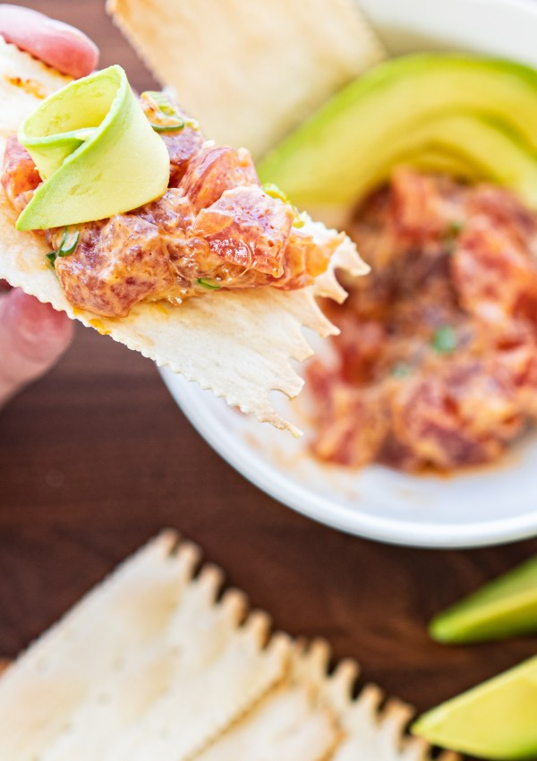 a woman's hand holding a cracker with a portion of spicy tuna tartare with avocado
