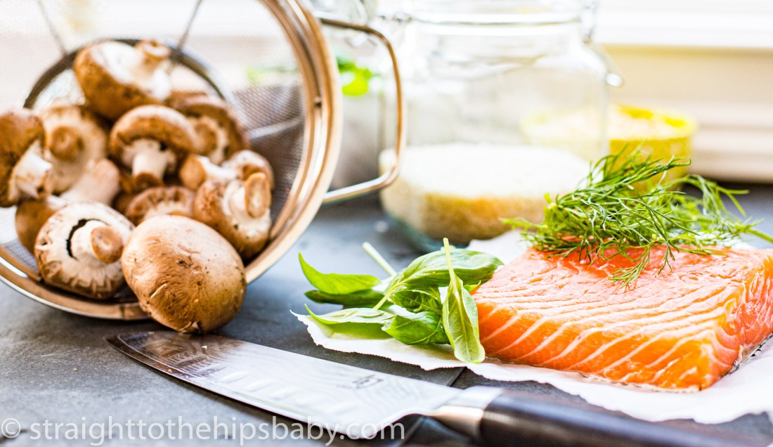 food flatly including a filet of pink/orange salmon, green herbs, fresh mushrooms and a jar of rice
