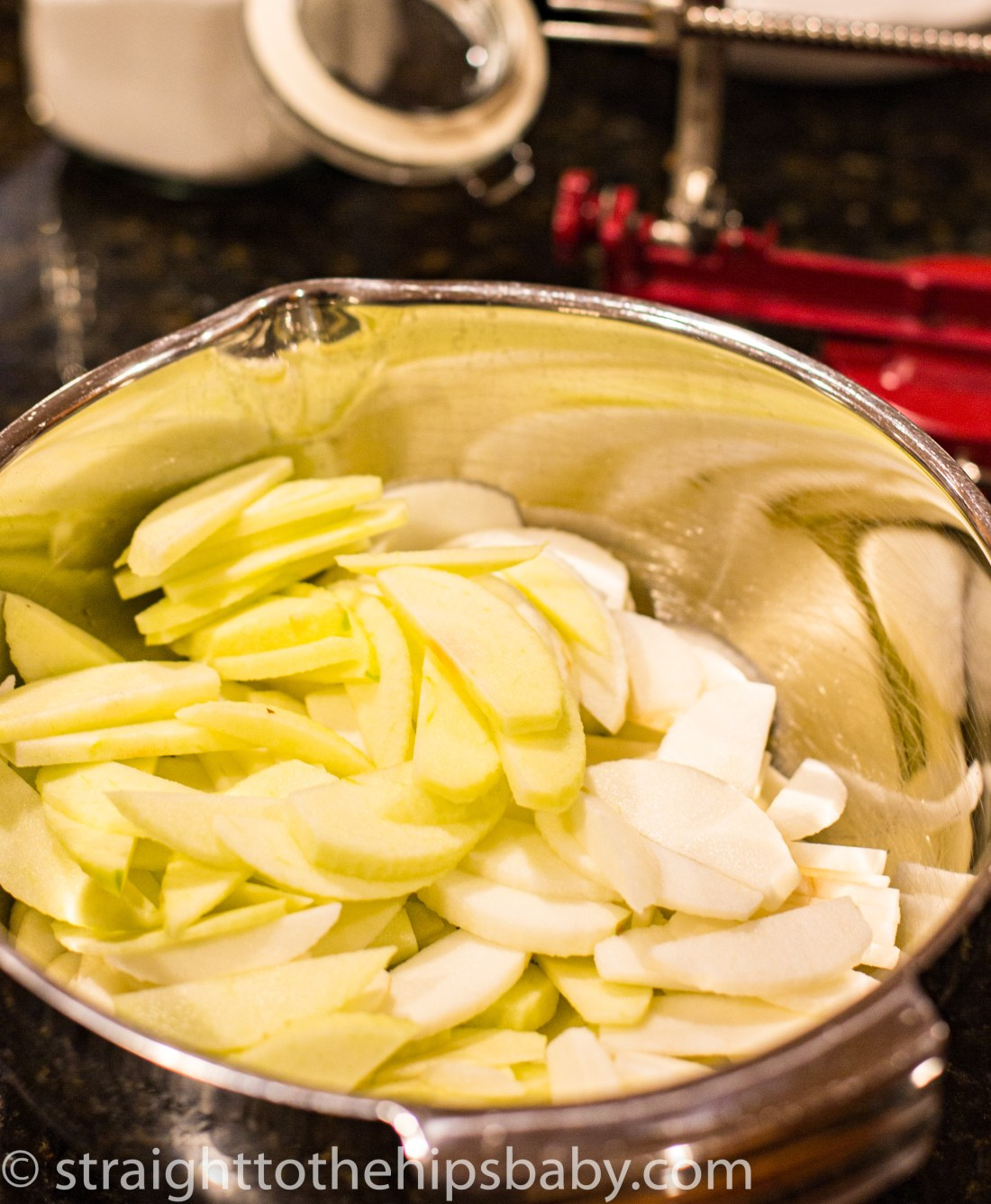 a large metal mixing bowl filled with sliced apples