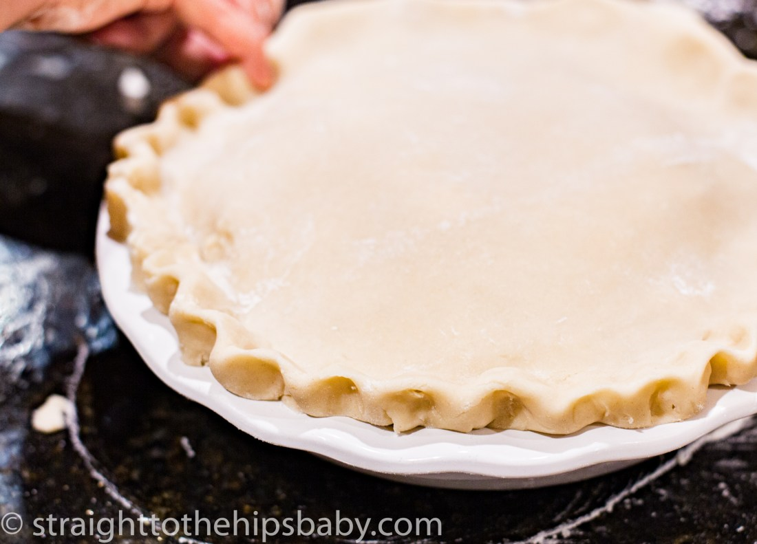 crimping the edges of the pie dough to seal