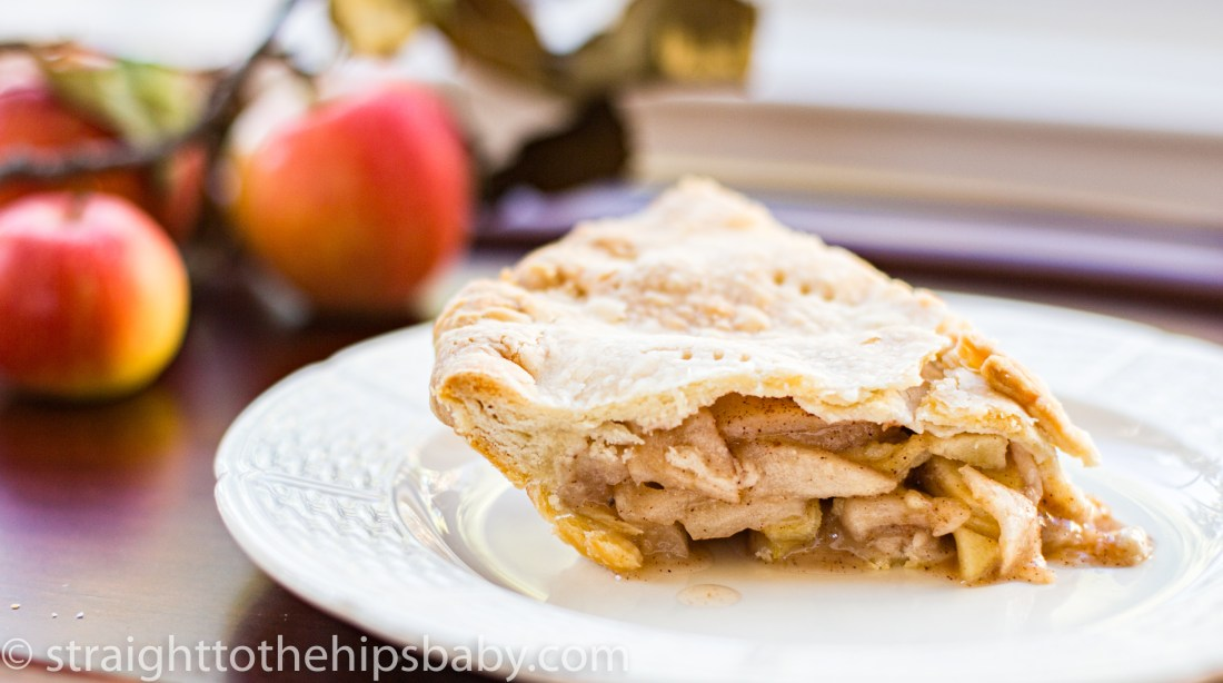 a slice of old fashioned apple pie on a white plate, with apples in the background