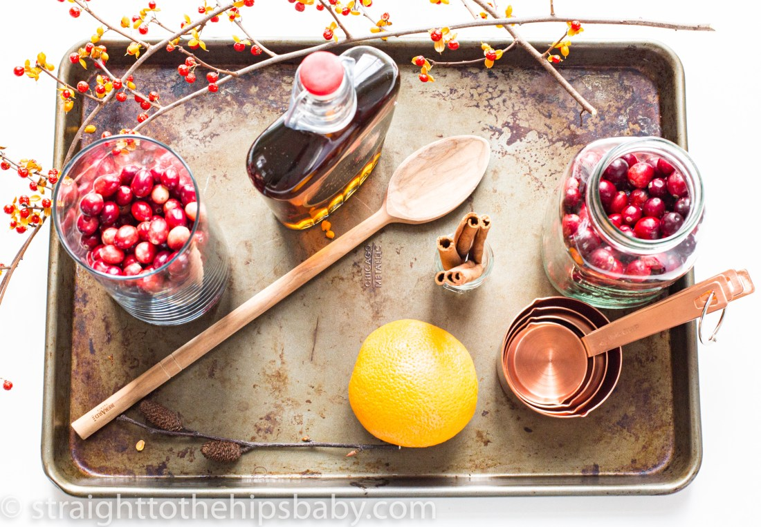 Ingredient shot featuring cranberries, maple syrup, and orange