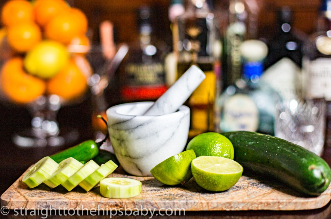 sliced cucumbers, limes and a mortar and pestle on a bar