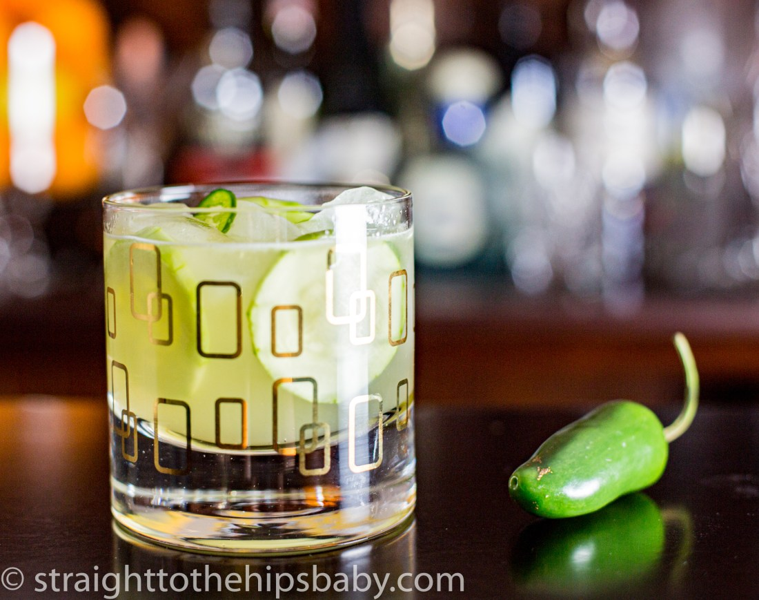a finished cocktail, light green with a round of cucumber, next to a whole green jalapeño pepper