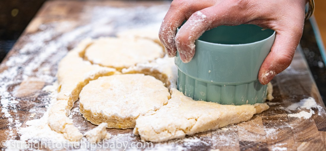 a woman's hand cuts round biscuits with a light blue biscuit cutter