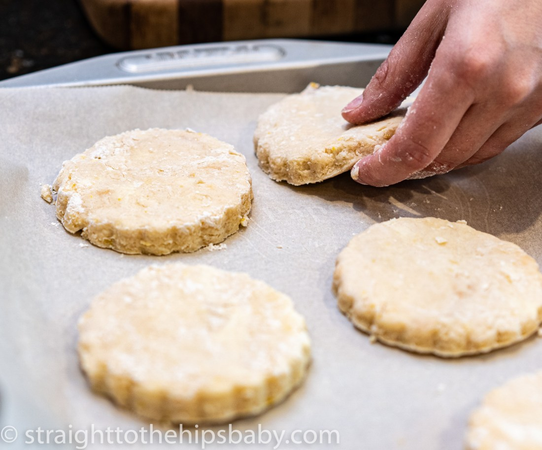 placing uncooked biscuits onto a parchment lined cookie sheet