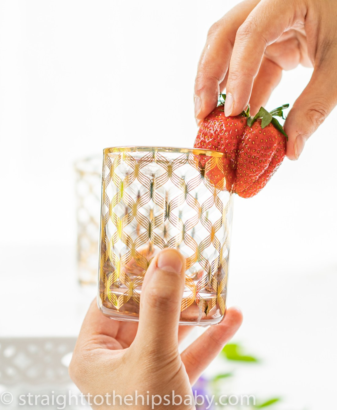 strawberry being run around the rim of a cocktail glass
