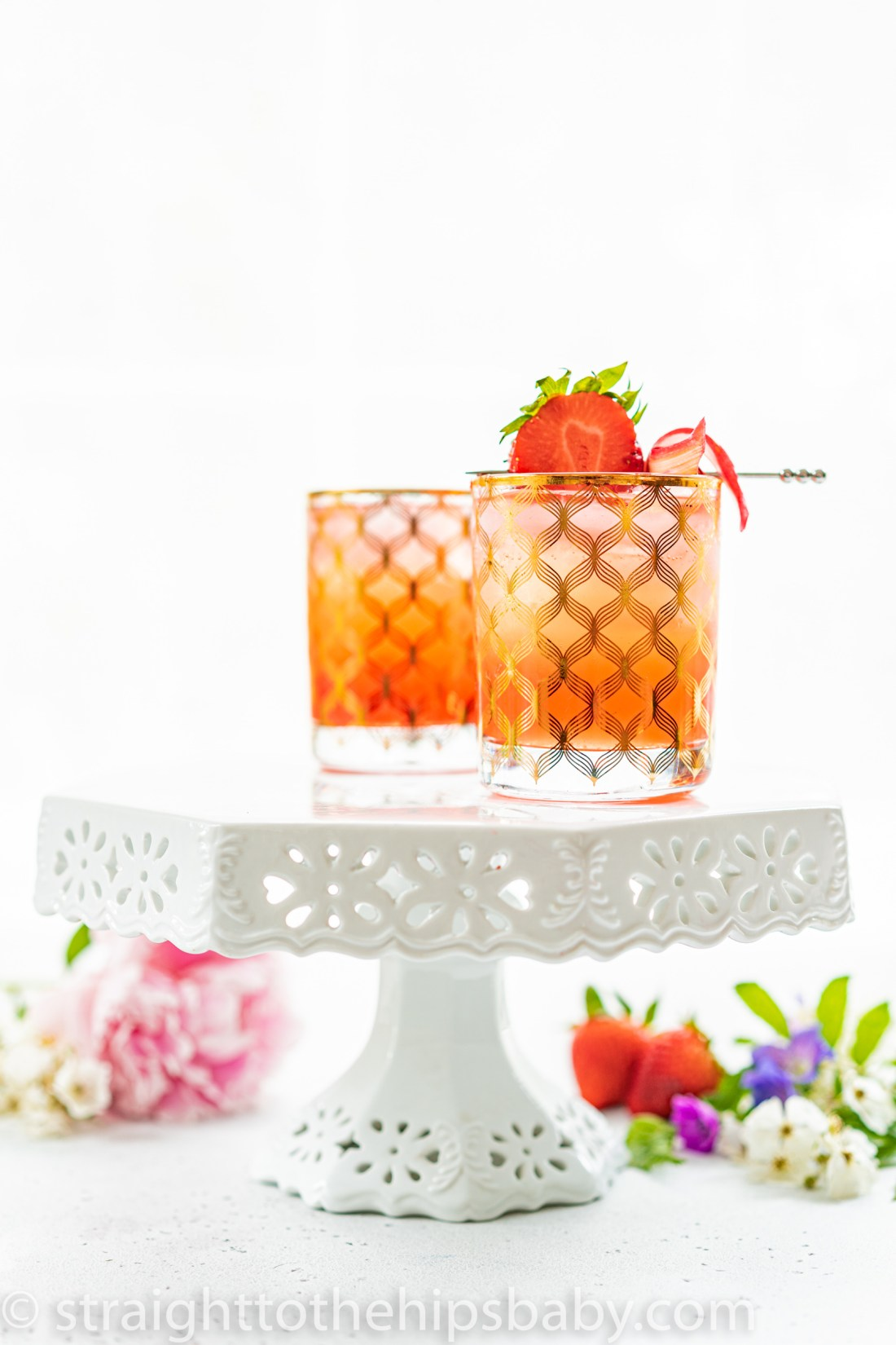 two cocktail tumblers filled with pink drinks and garnished with fresh strawberries