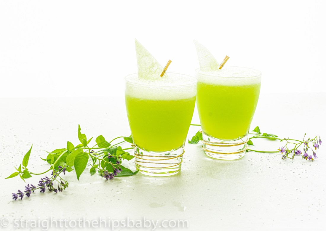 2 bright green frozen midori melon ball cocktails on a light background with a floweringvine