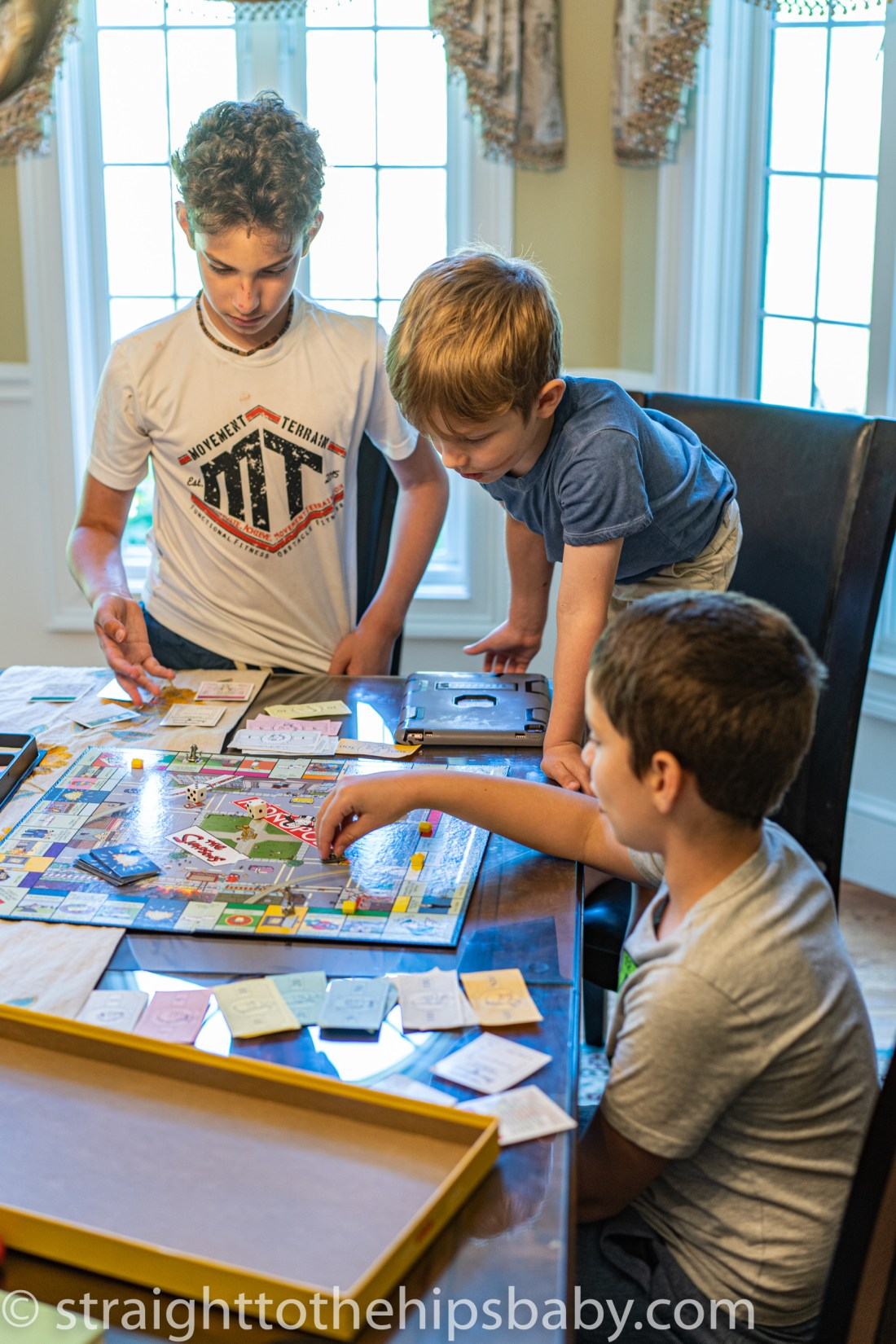 three young children playing board games around a large table
