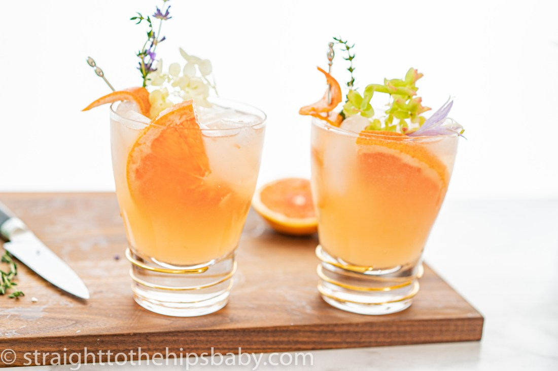 two pink grapefruit Paloma cocktails on a wooden cutting board. Topped with floral garnishes