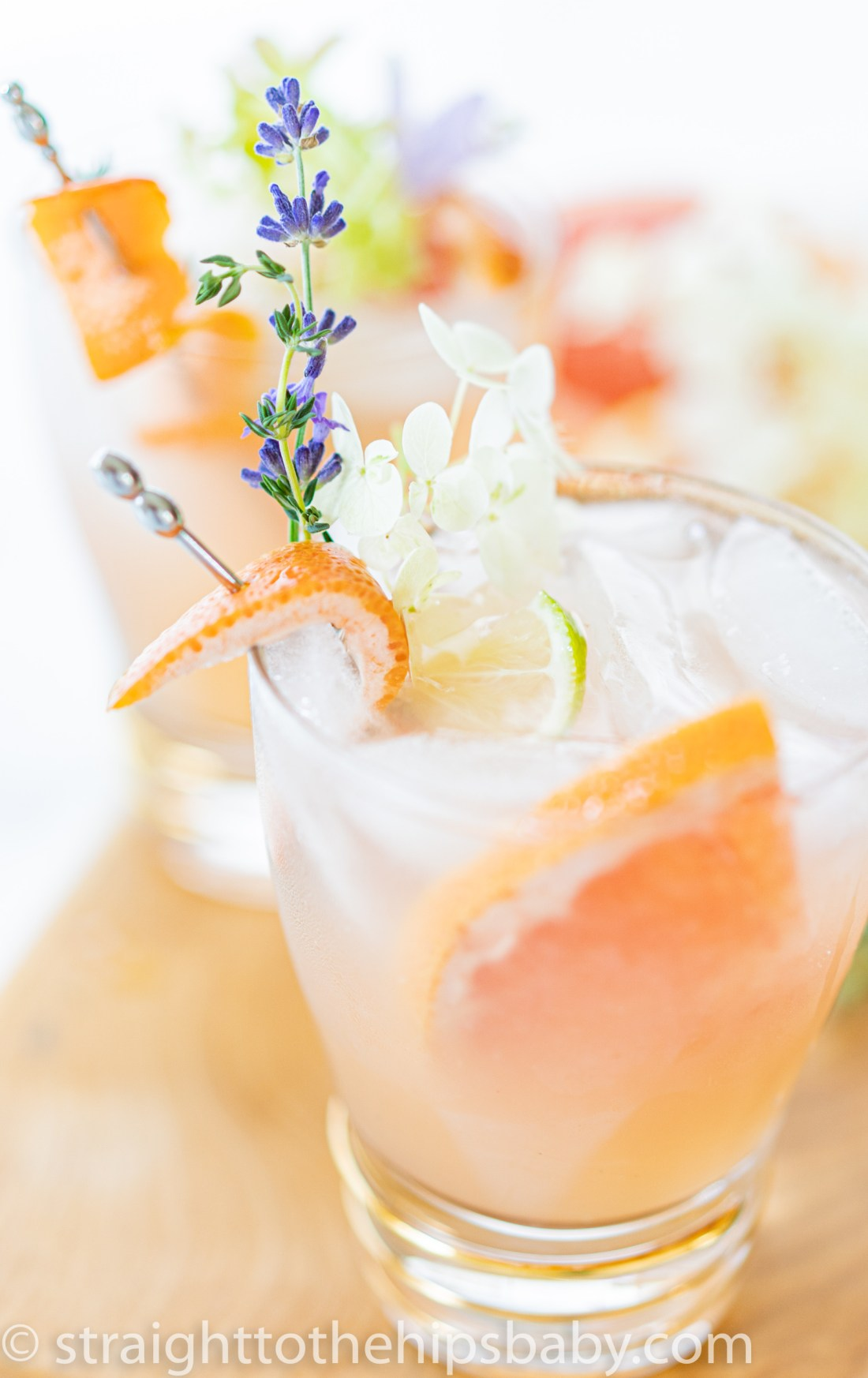 a beautiful light pink grapefruit Paloma tequila cocktail with delicate floral garnish