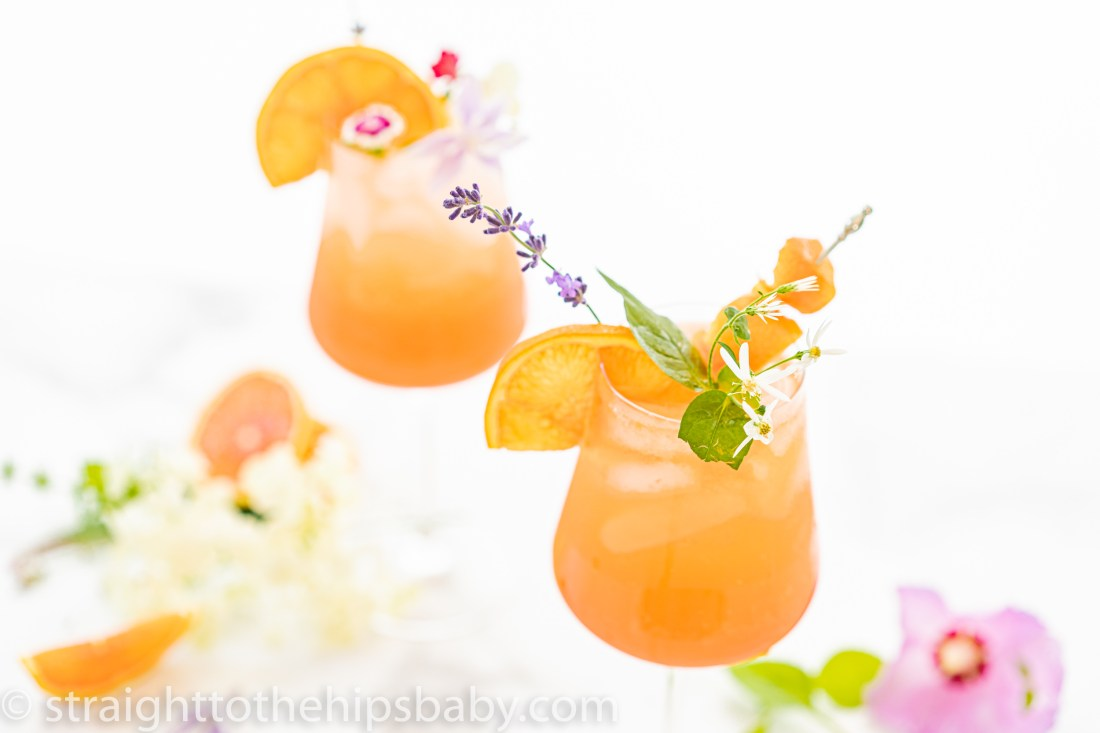 large wine glasses filled with an orange colored cocktail with lush flower garnishes