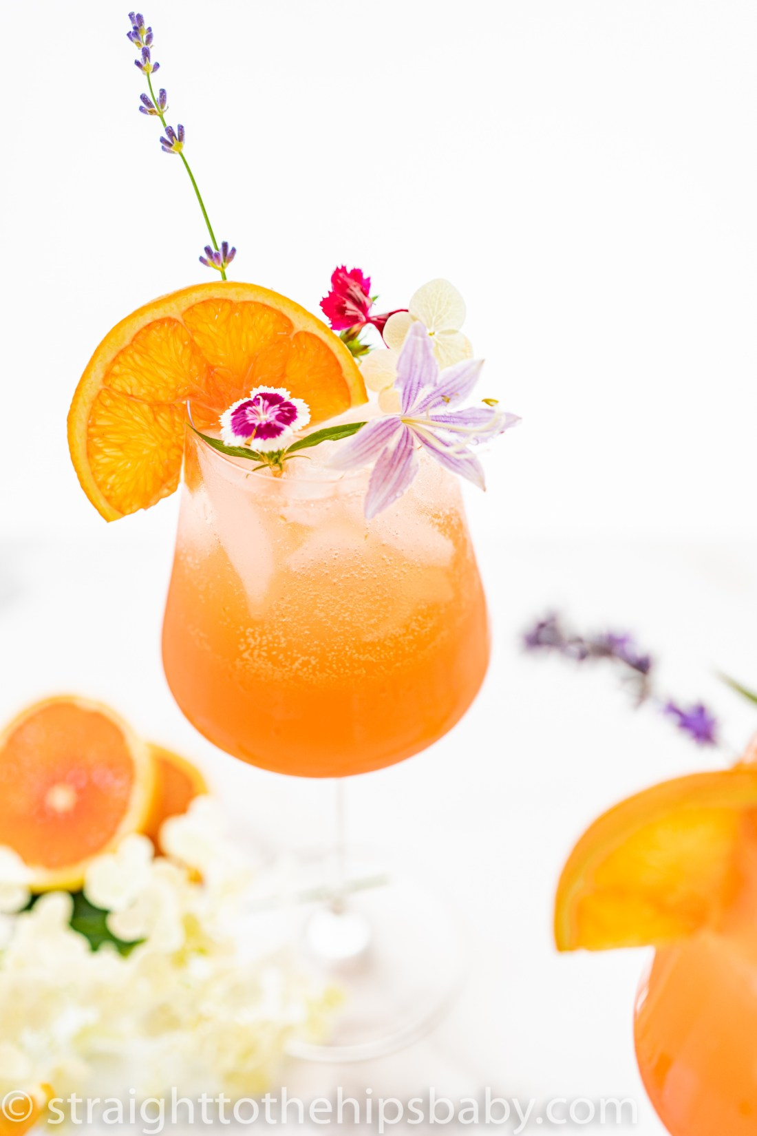 An icy cold finished grapefruit Aperol Spritz with an orange slice and lavender flower garnish