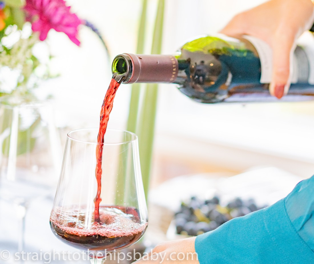 pouring a large glass of red wine