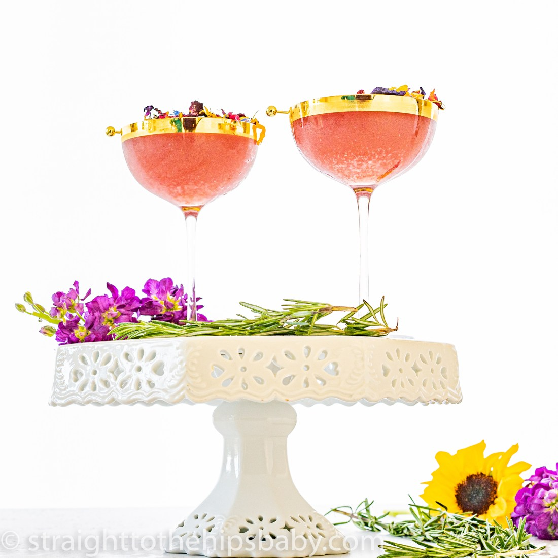 two finished cocktails sitting on top of a white vintage cake stand