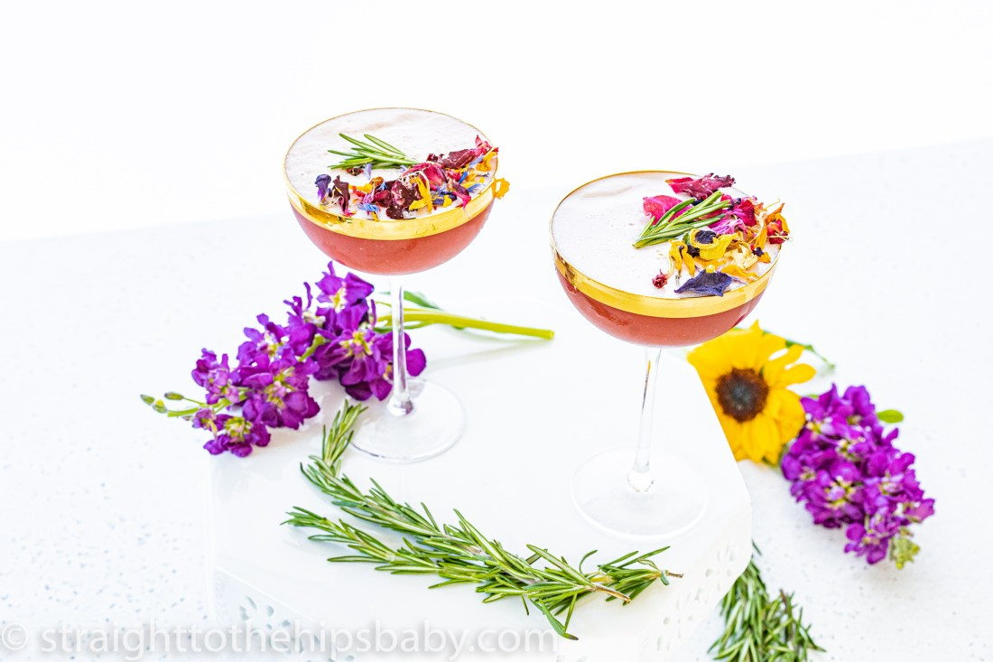 2 festive cocktails in gold rimmed coupe glasses