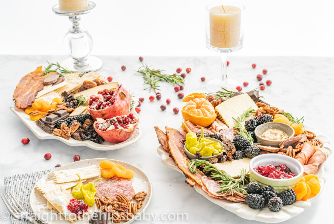 two laden charcuterie boards filled with brightly colored meats, cheese, and fruits on a white marble background, with candles in the background