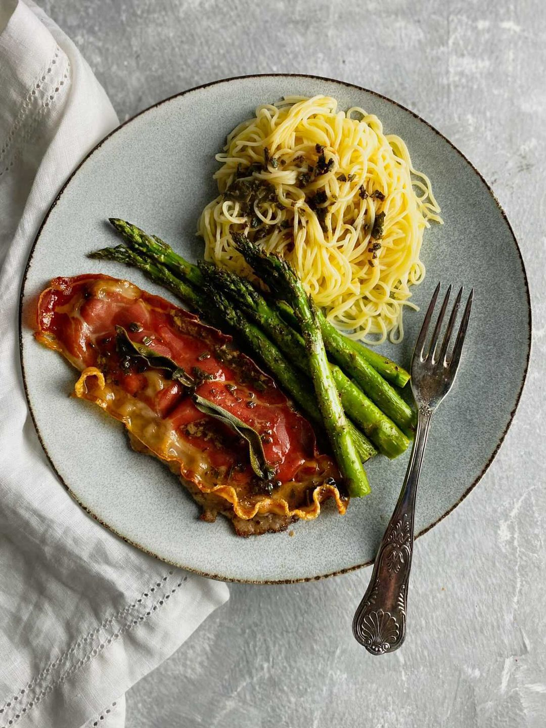 a blue plate with veal, asparagus, and angel hair pasta