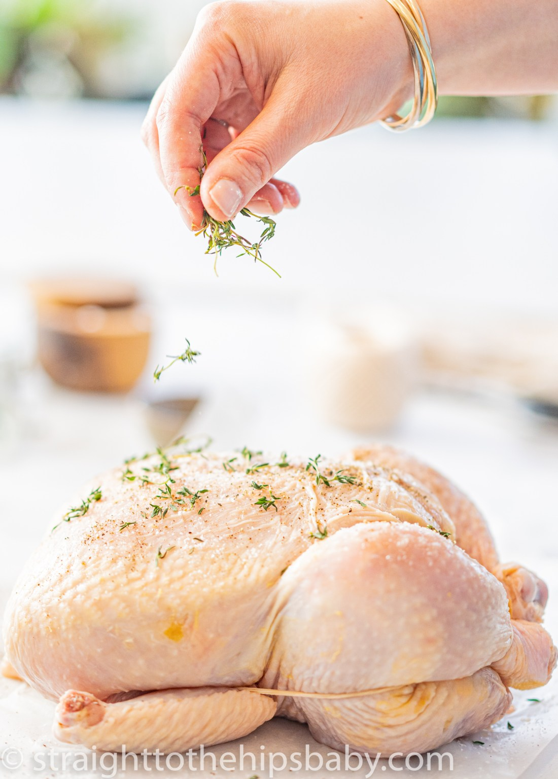 sprinkling fresh thyme leaves on top of a trussed whole raw chicken before roasting