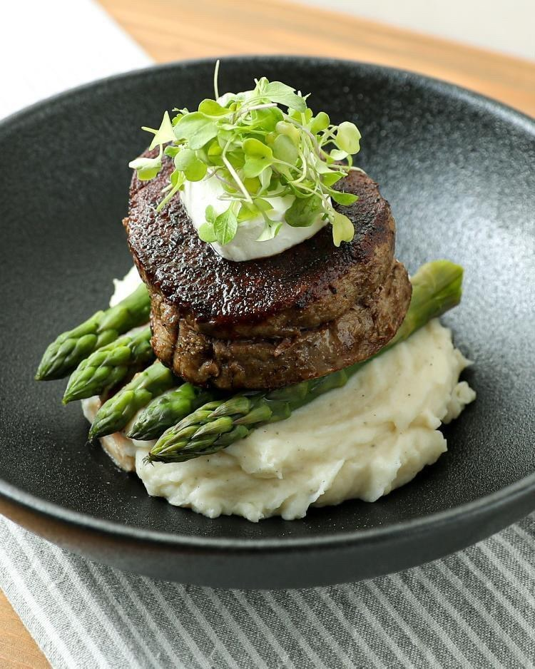 beautifully plated seared steak fillet on top of asparagus and creamy mashed potatoes on a black plate