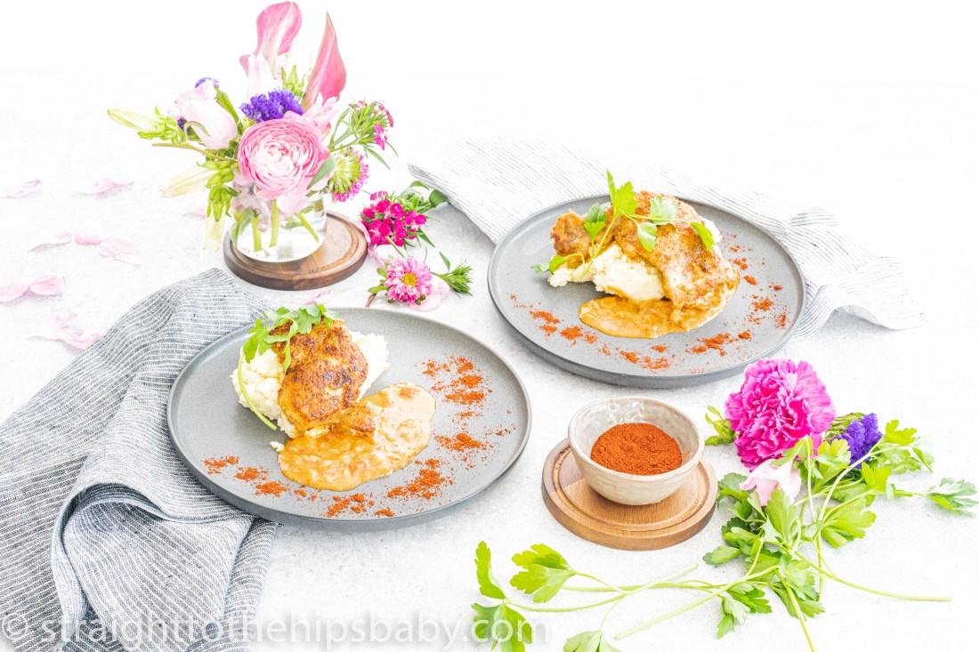 two dark grey plates of orange red chicken paprikash, surrounded by brightly colored pink flowers and greens.