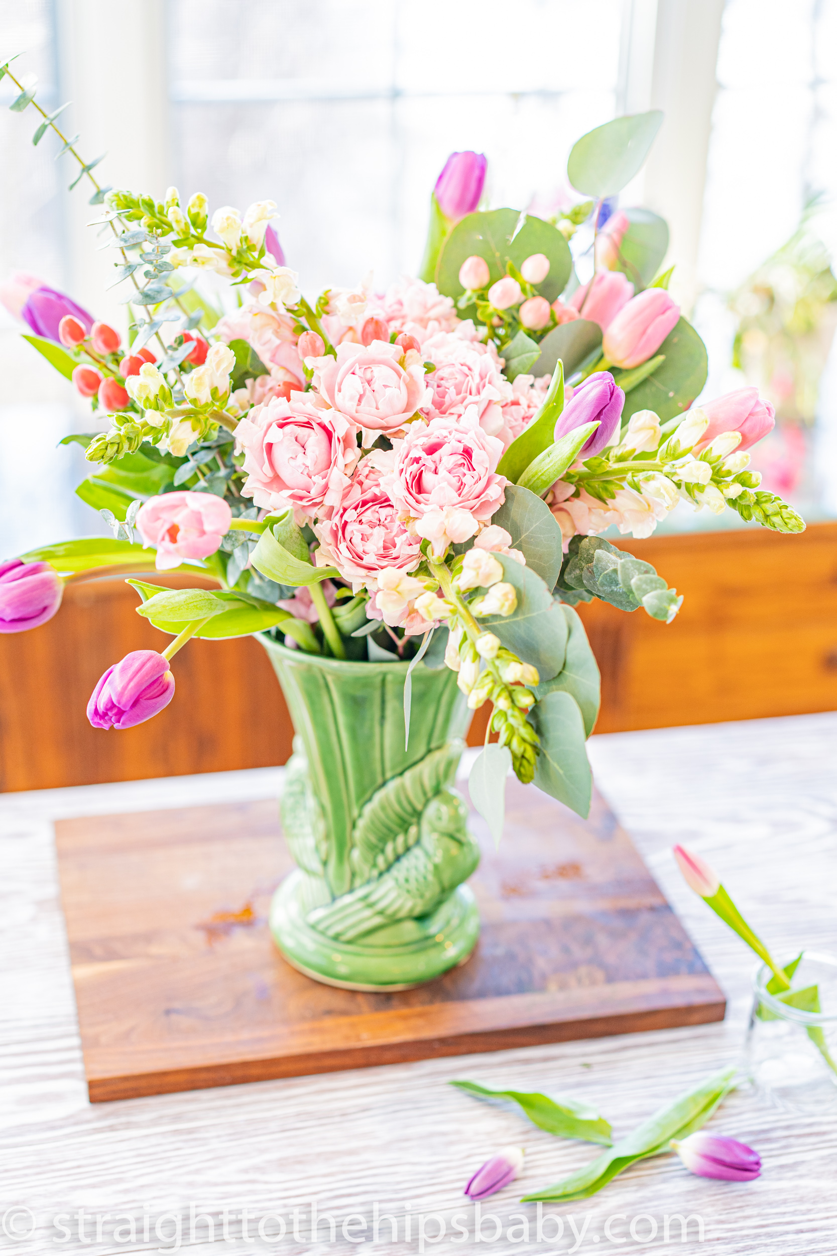 a finished pastel passover flower arrangement, in a green tall vase