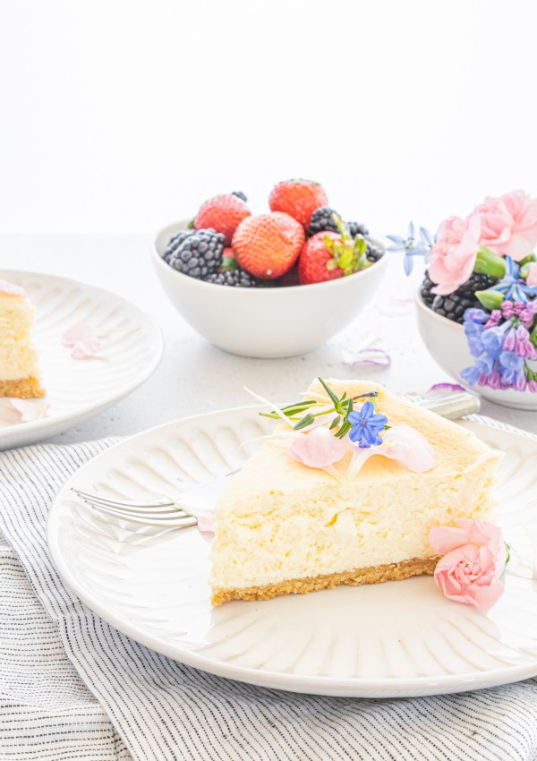 a single slice of keto gluten free sesame cheesecake on a white plate, garnished with flowers