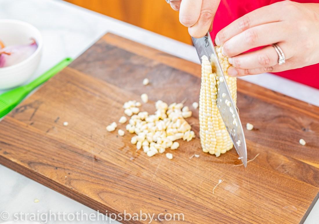 a woman slicing an ear of corn